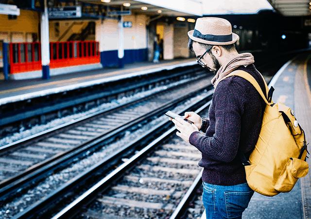 Man at Railway Station Typing on Phone