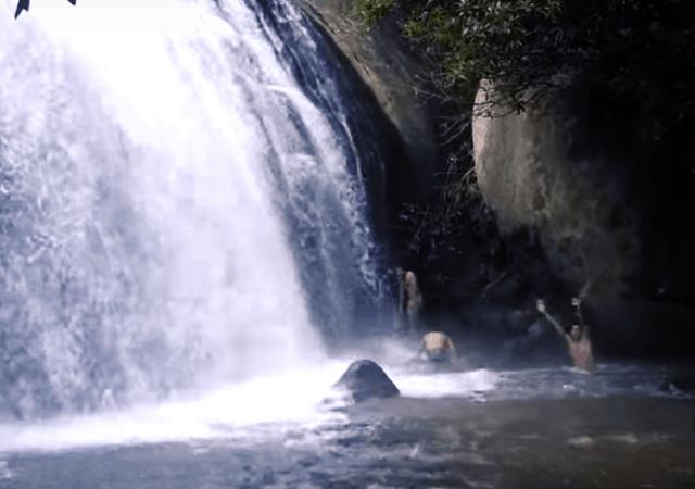 Travelers playing in Anayadikuthu Waterfall